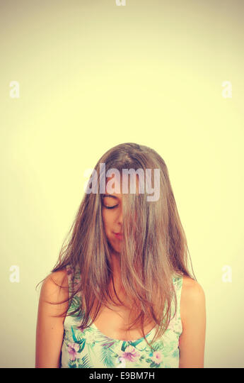 portrait of a young brunette woman with her hair in her face and her eyes closed, with a retro effect - Stock-Bilder