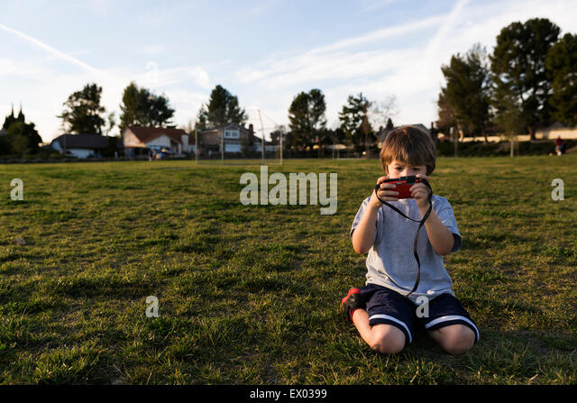 Boy kneeling in park looking at digital camera - Stock Image