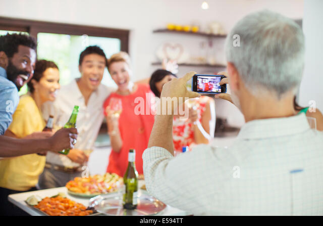 Friends taking picture together at party - Stock Image