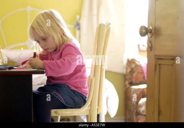 British toddler doing homework in bedroom London UK with atmospheric feel of victorian house and sunshine daylight. - Stock-Bilder