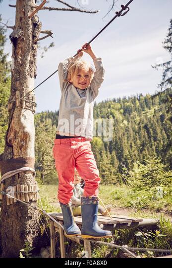 Young boy walking across single rope bridge - Stock Image