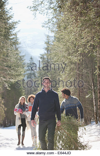 Four friends with gifts and Christmas tree in snow - Stock Image