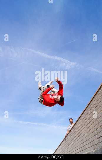 A parkour athlete performs a side flip over a wall. - Stock Image