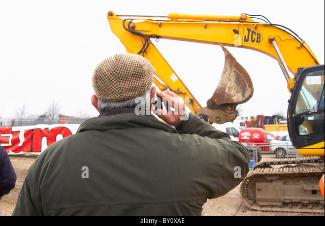 Man wearing flat cap and using mobile phone at plant auction - Stock Image