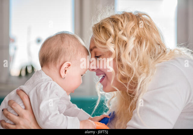 Mother and her baby head to head - Stock Image