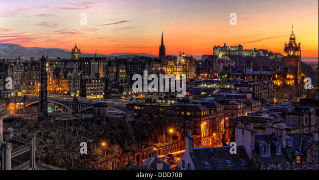 View over Edinburgh city at sunset showing buildings, castle, bridges and churches etc, Scotland - Stock Image