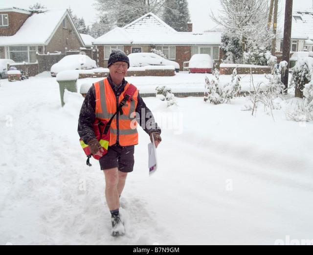 Cheery Postman wearing shorts during a snow storm. Biggin Hill, Bromley, Westerham, Kent England, UK. - Stock Image