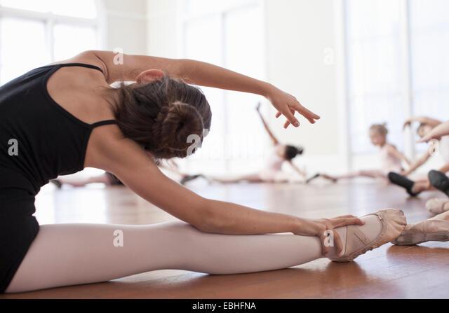 Children sitting on floor practicing the splits in ballet school - Stock Image