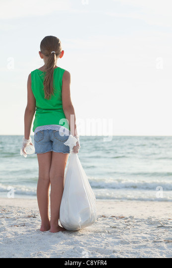 USA, Florida, St. Petersburg, Rear view of girl (10-11) standing on beach with garbage bag, facing ocean - Stock Image