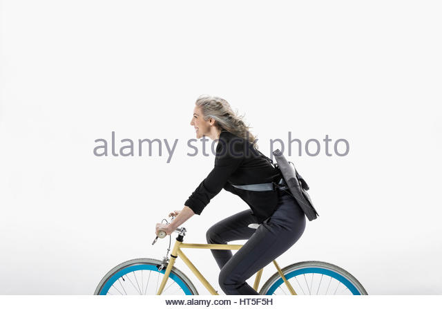 Smiling businesswoman riding bicycle against white background - Stock-Bilder
