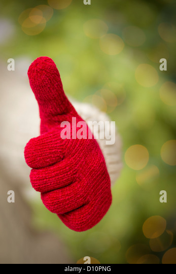 Woman in Sweater with Seasonal Red Mittens Holding Out a Thumb Up Sign with Her Hand. - Stock Image
