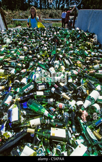 Empty beer and wine bottles at a recycling collection point with a woman throwing one more onto the pile, New Zealand - Stock Image