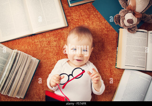 One year old baby with spectackles and a teddy bear - Stock Image