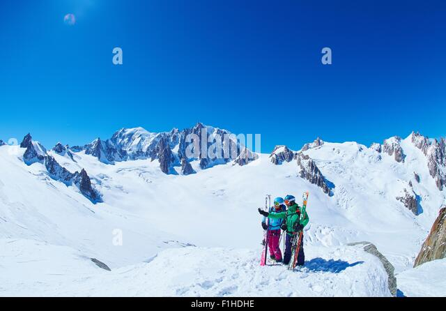 Mature male and female skiers on ridge at Mont Blanc massif, Graian Alps, France - Stock Image