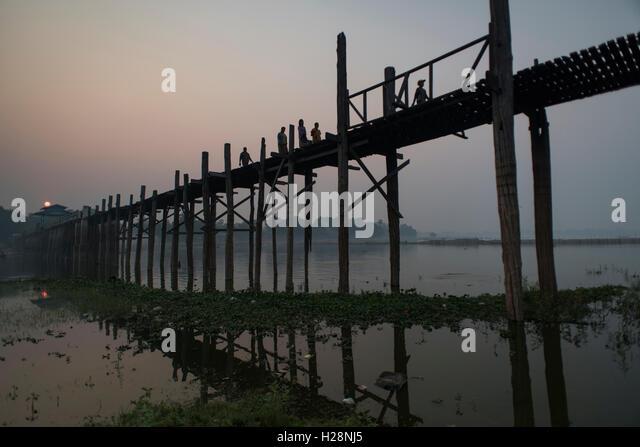 People crossing the U Bein Bridge at sunrise time, Amarapura, Myanmar. - Stock-Bilder
