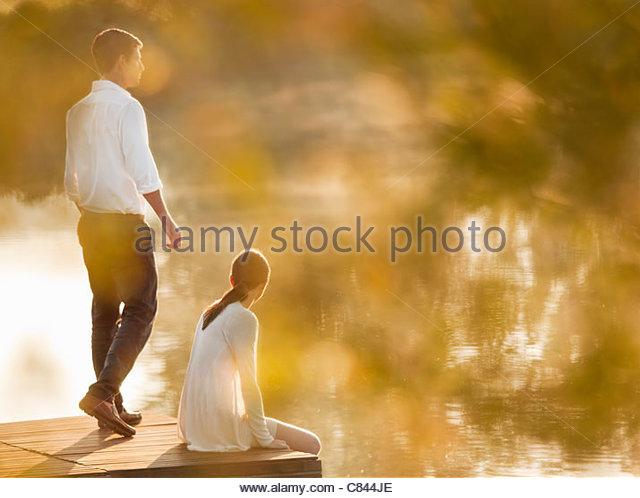 Couple relaxing on dock of lake - Stock Image
