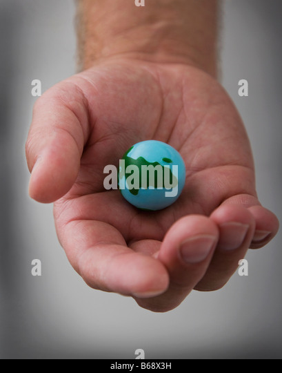 Man's hand holding small globe, close-up - Stock Image