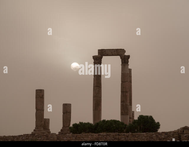 Sun behind a sand storm cloud by the Amman Citadel Temple of Hercules - Stock Image