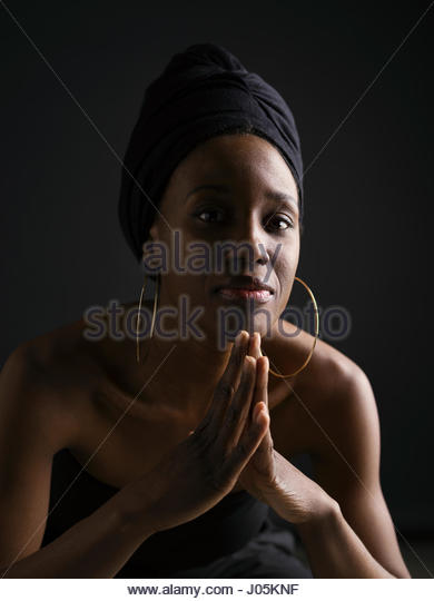 Portrait confident African American woman in headscarf and hoop earrings against black background - Stock Image
