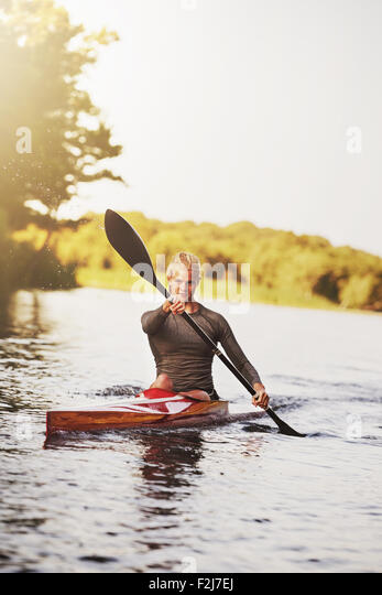 Athletic young blond woman sitting in the kayak while paddling with a double-bladed paddle on the still surface - Stock Image