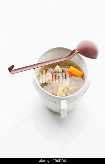 Beef broth in stew pot with ladle on white background - Stock Image