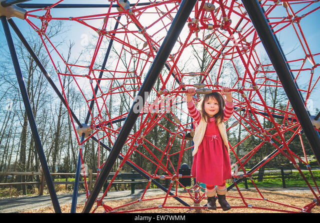 Girl playing on a red climbing frame - Stock Image