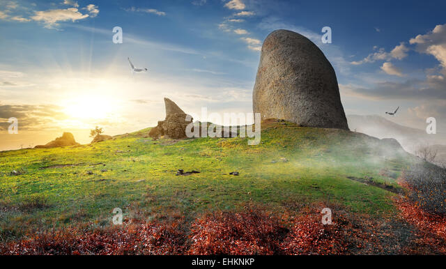Birds over big stone on mountain in autumn - Stock Image