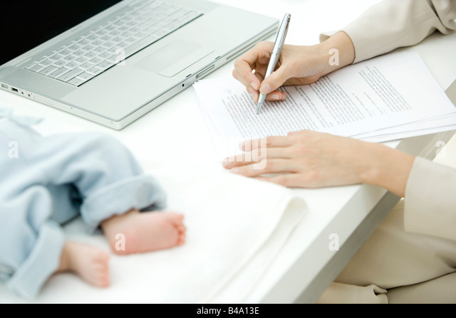 Woman editing document at desk, infant lying nearby, cropped view - Stock Image