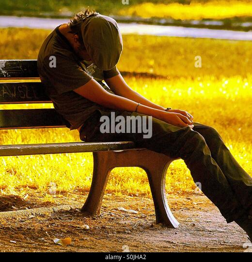 Man sleeping on bench - Stock Image