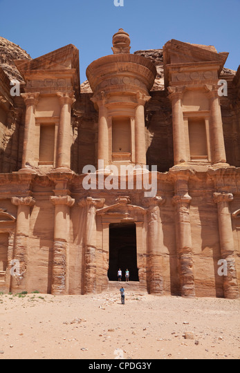 Tourists being photographed at the facade of the Monastery carved into the red rock at Petra, Jordan, Middle East - Stock Image