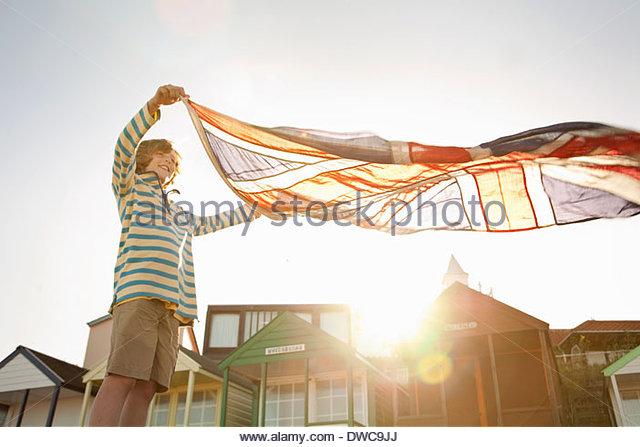 Boy holding up union jack flag at beach, Southwold, Suffolk, UK - Stock Image