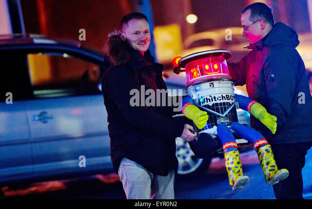 Munich, Germany. 13th Feb, 2015. The 'hitchBOT' robot is loaded into the car by Martin (L) and Bernd, who - Stock Image