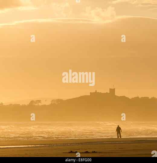 Man alone on beach - Stock Image