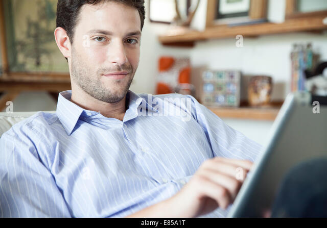 Man using digital tablet at home - Stock-Bilder