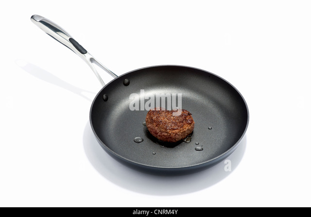A heart shaped beef burger in a frying pan - Stock Image