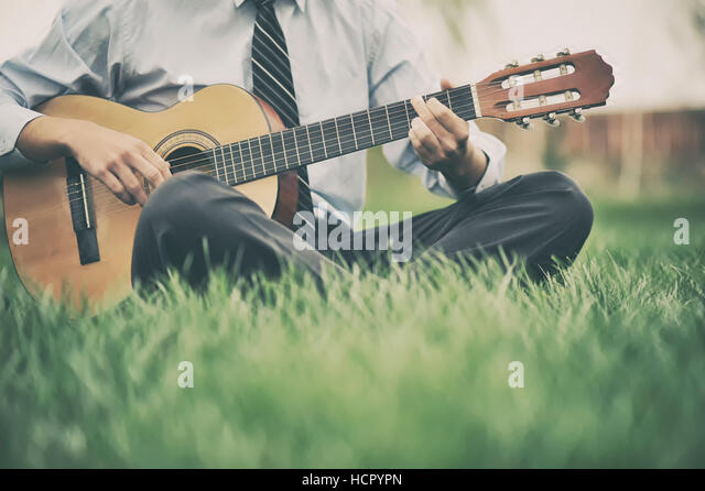 Young man playing the guitar in the grass - Stock Image
