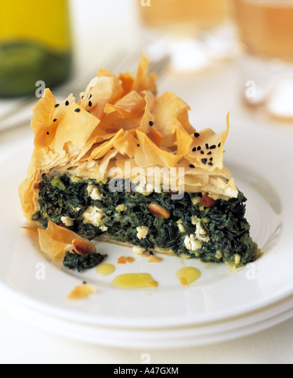 A slice of spinach filo pastry pie on a plate in a table setting vegetarian editorial food - Stock Image