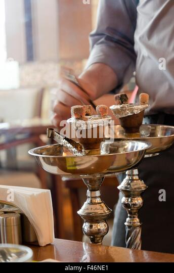Preparing the shisha, aka nargile or hookah at a restaurant by placing the charcoals on top. A very middle eastern - Stock-Bilder