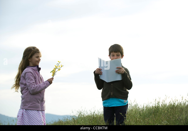 Children in field, boy reading book while girl picks wildflowers - Stock Image