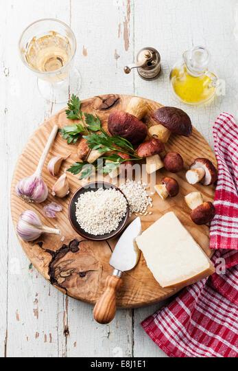Ingredients for risotto with wild mushrooms on wooden background - Stock Image