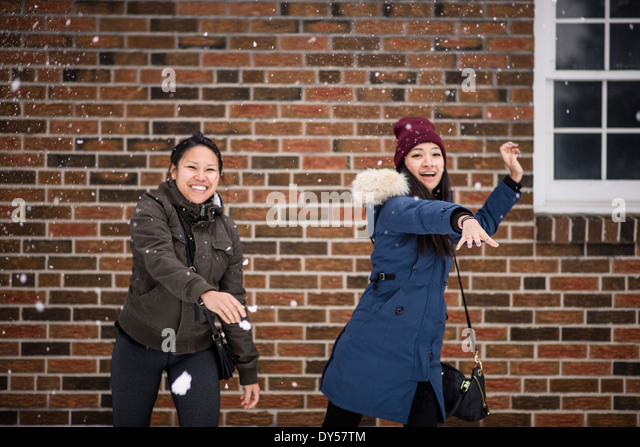 Two you adult females throwing snowballs - Stock Image