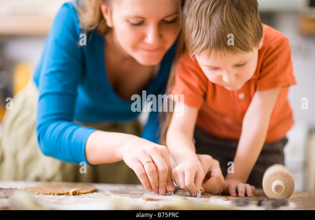 Young mother and son in kitchen making cookies - Stock-Bilder