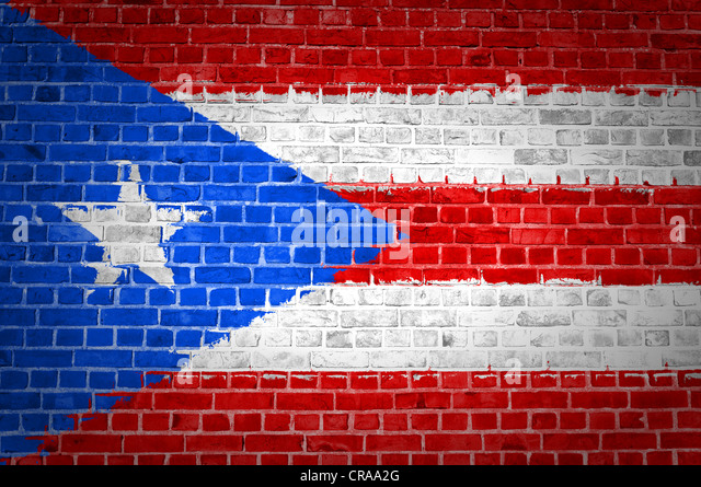 An image of the Puerto Rico flag painted on a brick wall in an urban location - Stock Image