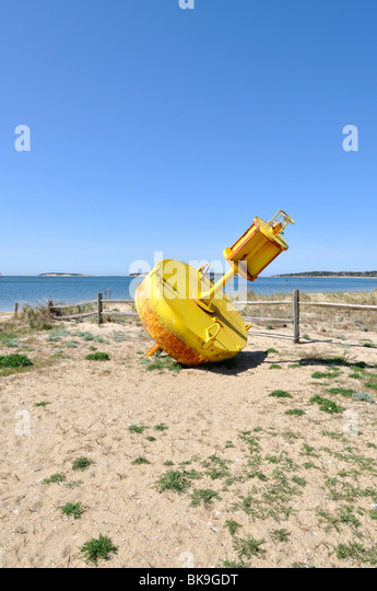 Yellow channel marker beached  in Wellfleet Harbor, Cape Cod USA. - Stock Image