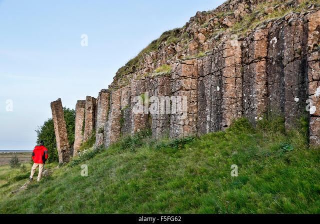 Hiker admiring columnar basalt outcrop, Dverghamrar (Dwarf Cliffs), near Foss, Iceland - Stock Image