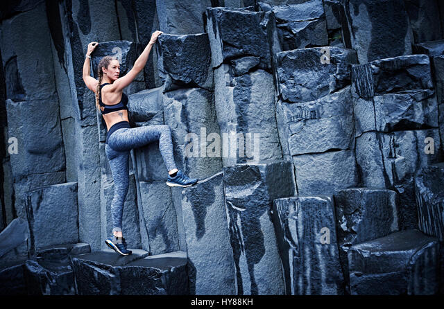 Happy confident young women climbing on basalt rock in southern Iceland - Stock-Bilder