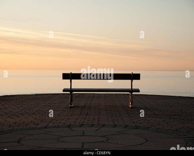 dusk, empty seaside bench on the promenade aberystwyth wales uk - Stock Image