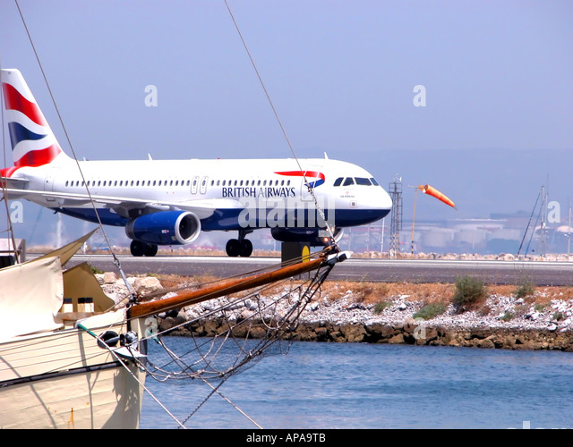 British Airways jet landing at Gibraltar airport, Marina Bay boats in the foreground, - Stock Image