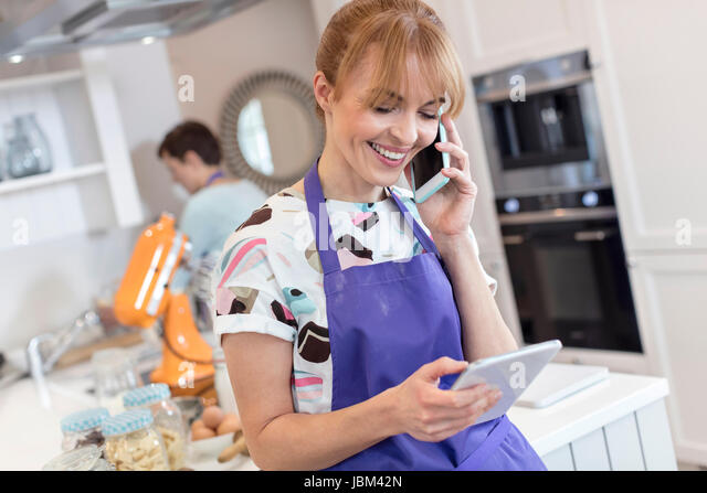Smiling caterer working, talking on cell phone and using digital tablet in kitchen - Stock-Bilder
