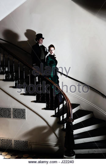 Victorian couple walking down staircase - Stock Image